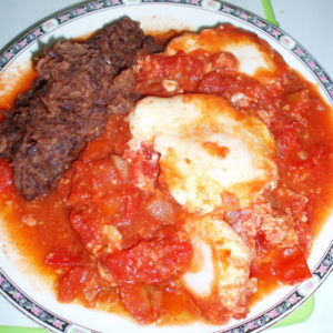 Plate of Eggs in Cooked Tomatoes, with Refried Beans