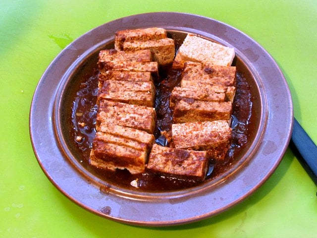 Plate of frozen and thawed tofu, soaking up sauce.