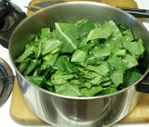 Filling the pot with chopped collards - www.inhabitedkitchen.com