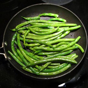 Saute fresh green beans in a pan.