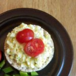 Egg salad on rice cake with tomatoes.