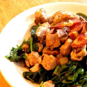 Serving bowl of pork with bacon and mushrooms, and baby greens
