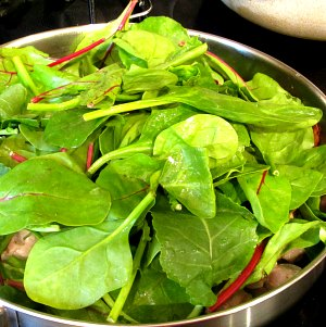 Adding baby greens to skillet