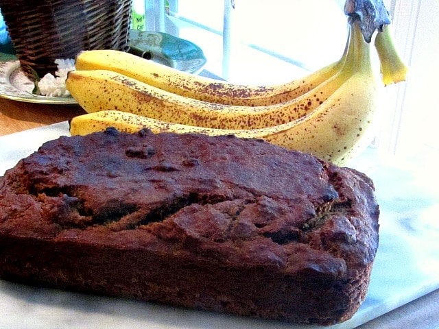 A loaf of fresh sugar free banana bread with ripe bananas.