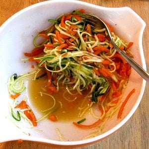 A bowl of spiralized zucchini and carrot, with liquid collecting in the bottom