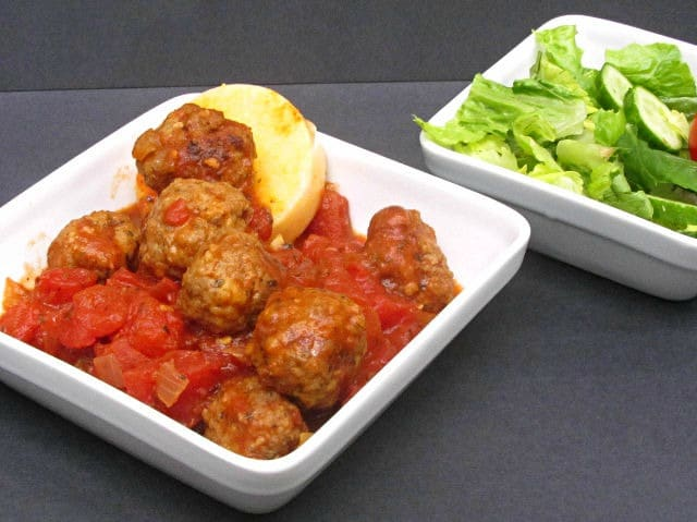 A dish with meatballs in tomato sauce, served over polenta.