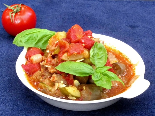 A dish of ratatouille with Italian sausage, garnished with basil