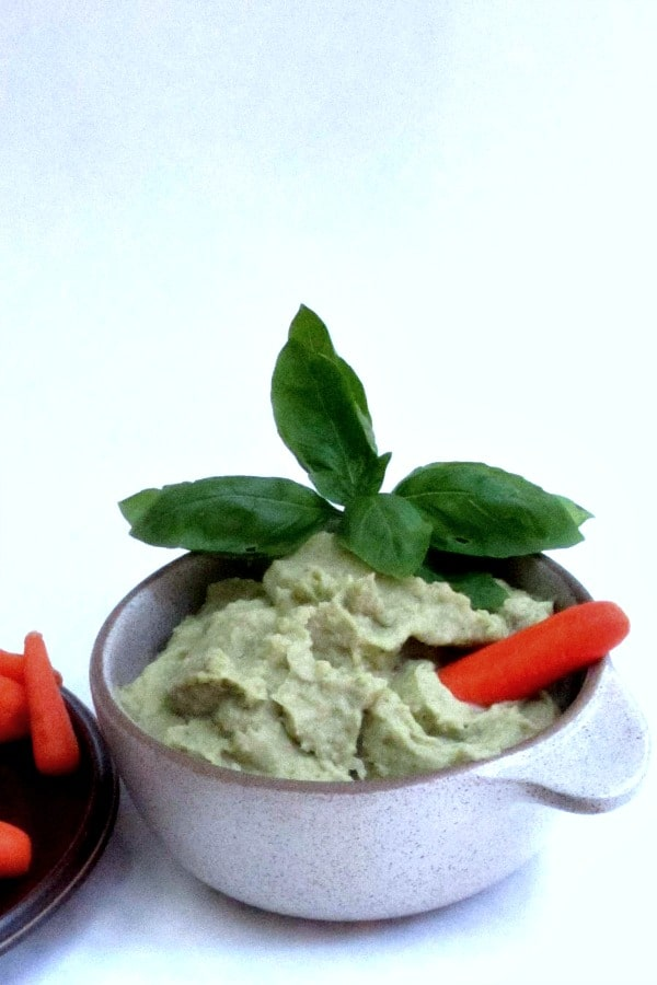 Bowl of Pesto Hummus served with baby carrots