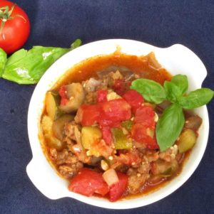 White dish of ratatouille with Italian sausage