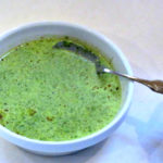 Bright green Cream of Spinach Soup in a white bowl.