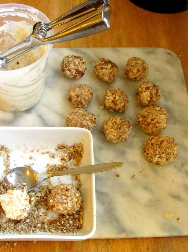 Rolling Onion Cheese Bites in chopped nuts.