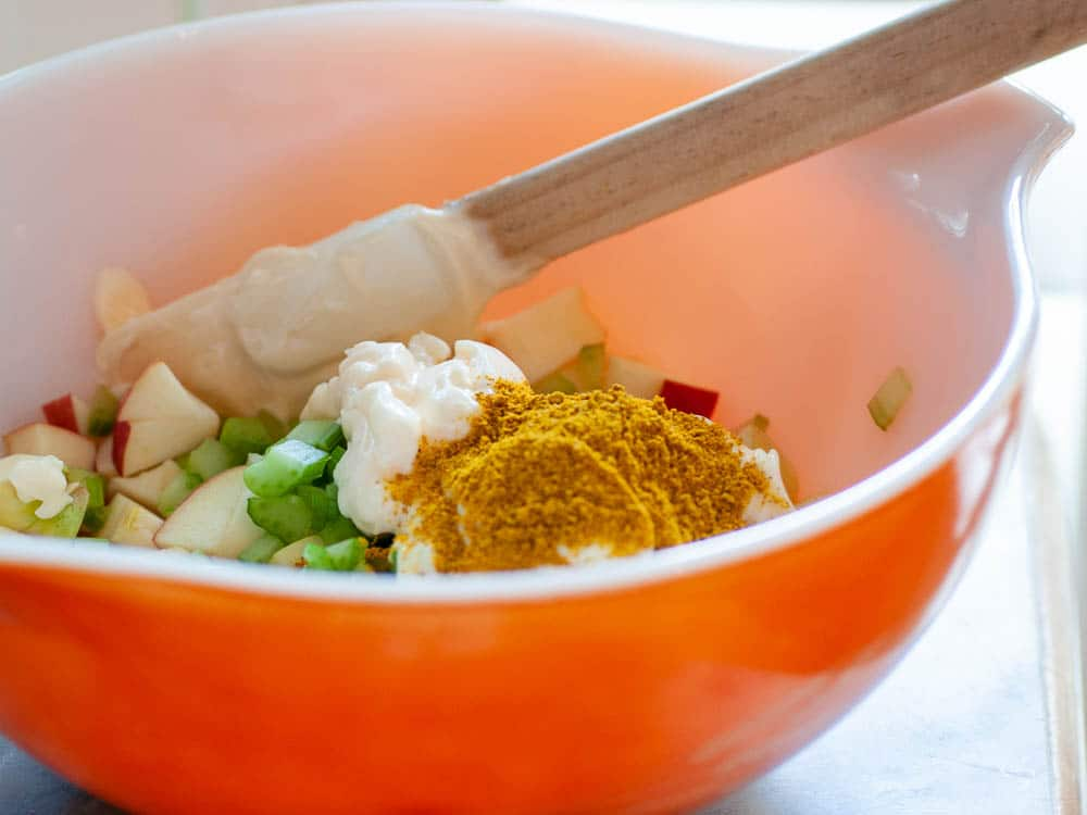Ingredients for curried chicken salad in a bowl.