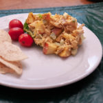 Curried Chicken Salad, plated with tomatoes and chips